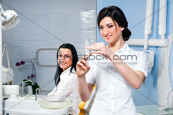 Attractive woman dentist with medical syringe and smiling patient