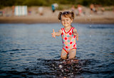 Adorable baby girl playing with a water in the sea