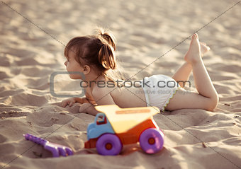 Adorable baby girl lying in the sand on the beach