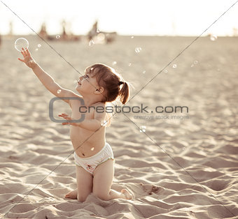 Adorable baby girl playing with soap bubbles on the beach