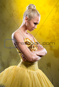 Sad ballerina in yellow tutu posing over obsolete wall