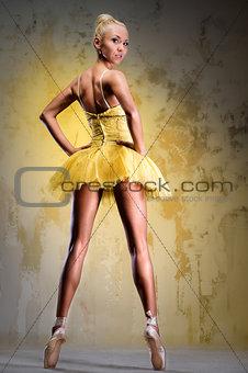 Beautiful ballerina in yellow tutu on point