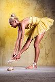 Beautiful ballerina in yellow tutu wearing pointe shoes