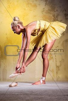 Beautiful ballerina in yellow tutu wearing pointe shoes