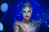 Beautiful woman with creative bright make-up over glowing lights