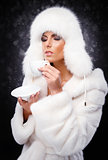 Beautiful woman in white fur coat and cap drinking coffee