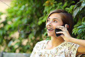 Casual happy woman on the phone in a park
