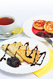 Food of Crepes, cheesecakes with berry sause and cup of tee.
