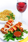 table with food of meat on skewer, dumplings and gass of red win