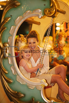 Portrait of happy mother and baby girl riding on carousel