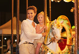 Happy mother and baby girl riding on carousel