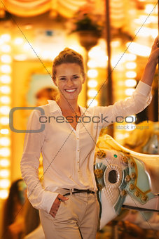 Portrait of smiling young woman riding on carousel