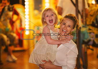 Portrait of smiling mother and baby girl in front of carousel