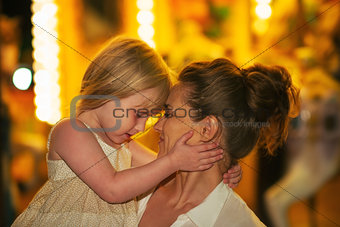 Portrait of mother and baby girl hugging in front of carousel