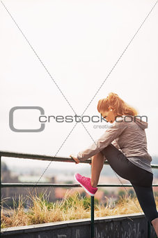 Fitness young woman stretching outdoors