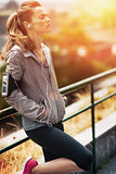Portrait of relaxed fitness young woman in city in the evening