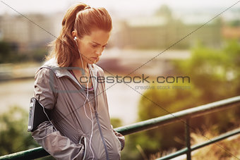 Portrait of fitness young woman in city in the evening