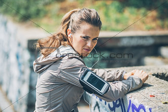Portrait of serious fitness young woman outdoors