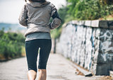 Closeup on fitness young woman jogging in the city park. rear vi