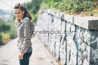 Portrait of serious fitness young woman in the city park