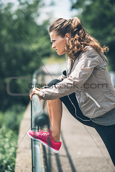 Fitness young woman stretching in the city park
