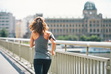 Fitness young woman jogging in the city. rear view
