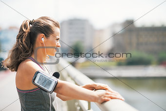 Fitness young woman in the city looking into distance