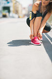 Closeup on fitness young woman tying shoelaces outdoors