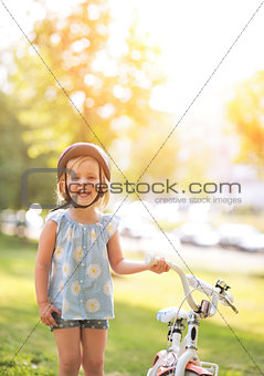 Portrait of happy baby girl with bicycle