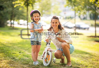 Portrait of happy mother and baby girl with bicycle