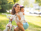 Portrait of baby girl hugging mother near bicycle in park