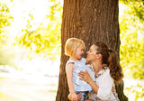 Portrait of happy mother and baby girl standing near tree