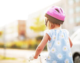 Baby girl riding bicycle. rear view