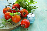 branch of fresh organic  tomatoes with green basil on wooden background