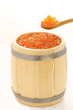 red salmon caviar in a wooden spoon and a barrel