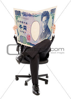 Business man sitting on a chair with japan currency in hands