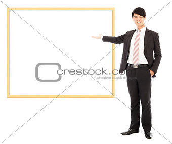 asian smiling business man pointing blank board