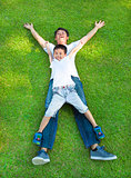 happy father and son lying on a meadow together
