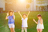 Happy kids has fun playing in water fountains