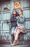 Two beautiful grunge girls standing at wall