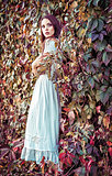 Beautiful young girl in white dress standing among colorful leaves