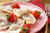 dumplings with berries and cream sauce served with fresh strawberries