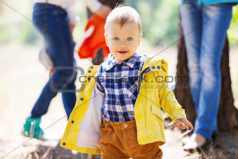 Toddler boy on bright autumn day, with blurred adults in the background