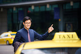 asian businessman calling taxi car leaving work
