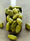 peeled green pistachio nuts on a wooden background