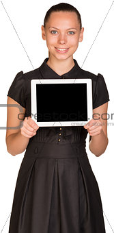 Beautiful girl in dress holding tablet and looking at camera