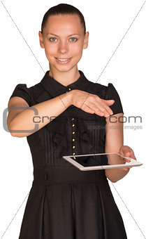 Beautiful girl in dress holding tablet and covers it