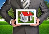 Hands hold tablet pc. Picture of small house with red roof on screen