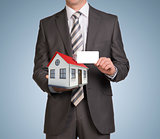 Businessman in suit hold empty card and small house