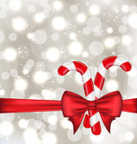 Christmas glowing background with gift bow and sweet canes